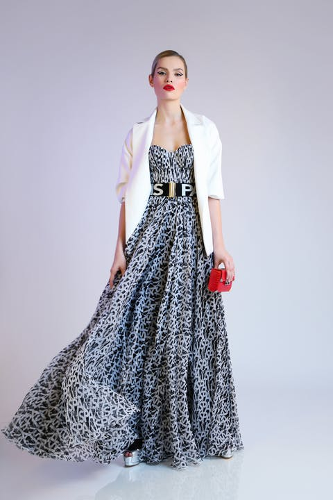 Black and white 'Paris' print silk chiffon strapless evening gown, accompanied by white wool crêpe jacket featuring plonge leather lapels. Scarlet alligator lisse Jolie crossbody bag with silver elaphe platform sandals and 'Paris' belt.