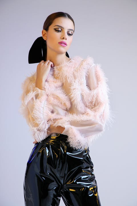 Powder pink organza blouse featuring crystal and feather embellishment, accompanied by black liquid PVC trousers.