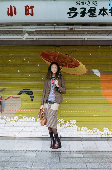 Jacket, ETRO. Shirt, HOPE. Kntwear, TORY BURCH. Earrings, TOGA PULLA. Bag, BALLY. Boots, CHLOÉ. Umbrella, WAGASA CASA.
